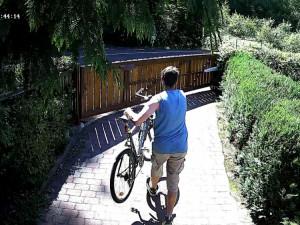 Muž odnáší kolo ze zahrady.